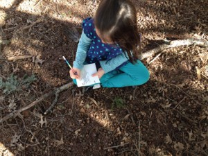 young student sitting outside sketching in a notebook