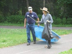Volunteers carrying trash along trail.