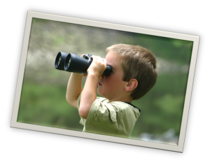 young child holding binoculars