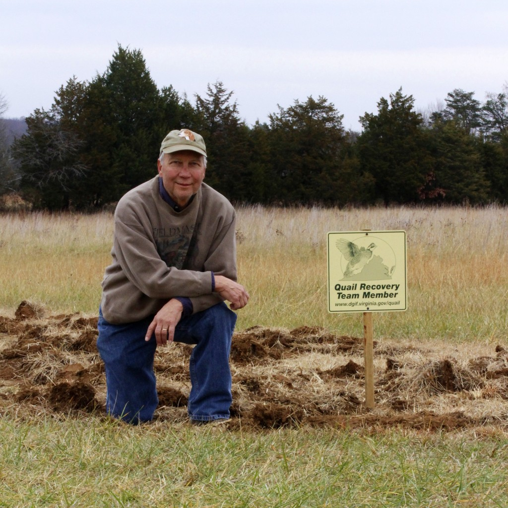 "volunteer kneeling in field next to a sign saying ""Quail Recovery Team Member"""