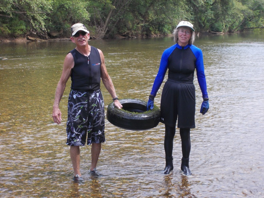two volunteers standing in river holding a car tire