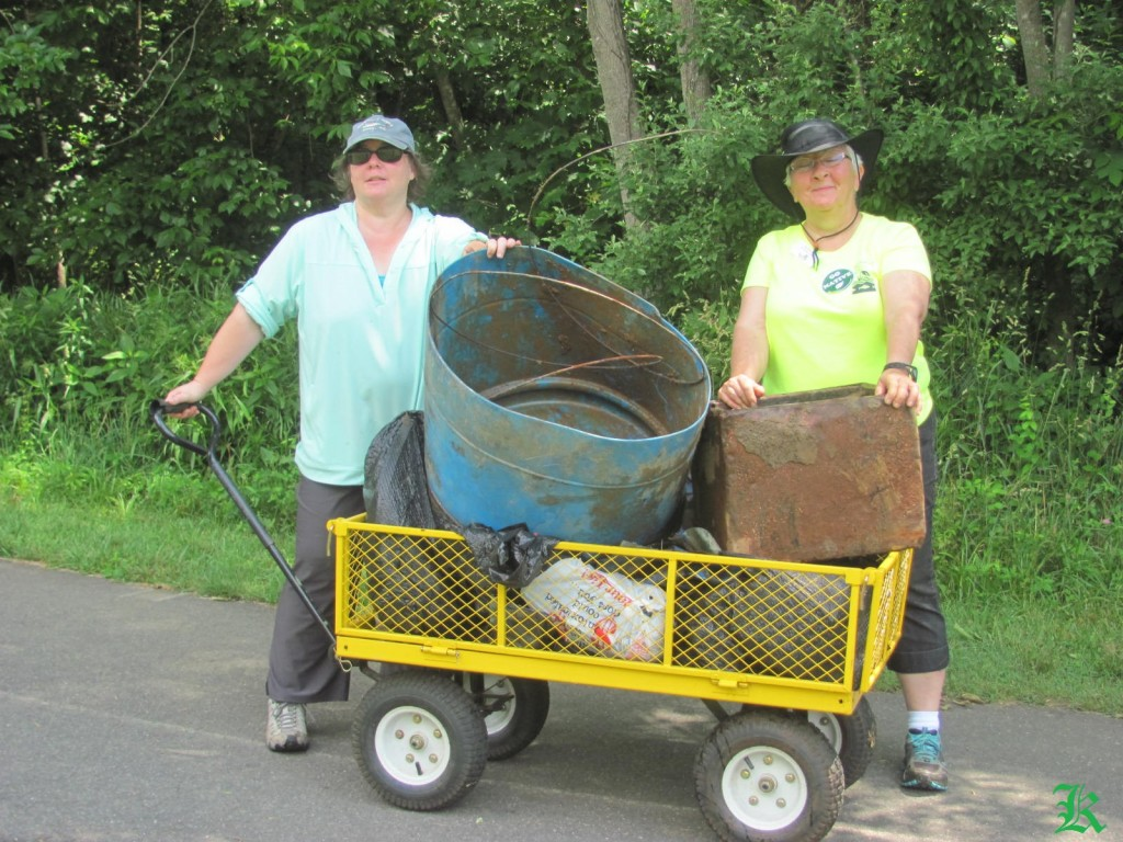two volunteers with a cart of trash they collected
