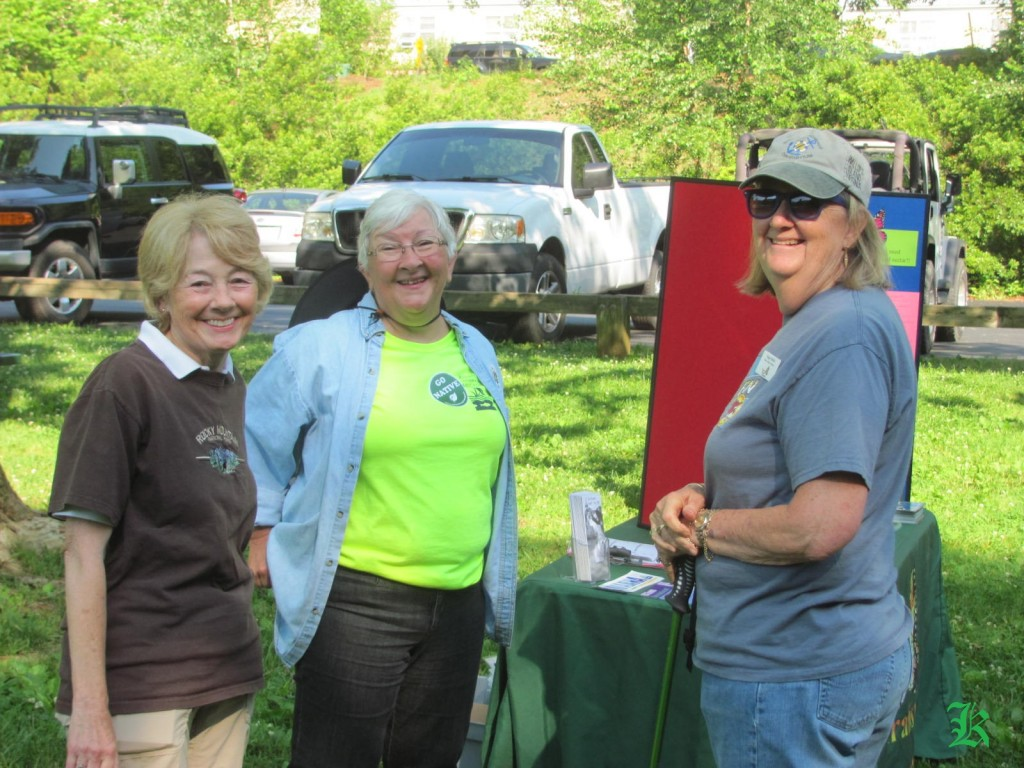 three smiling volunteers next to a table with a display