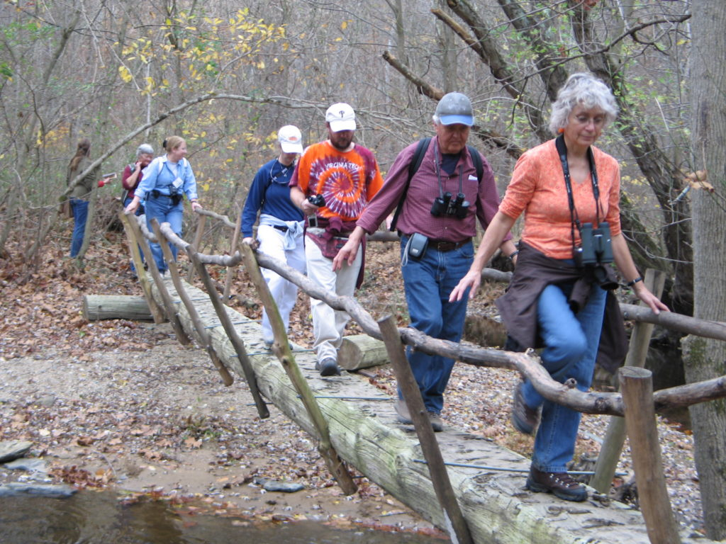 volunteers crossing wooden bridge on a hiking path